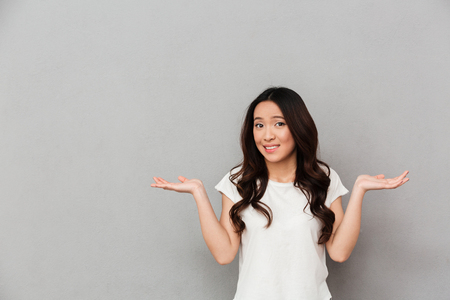 Portrait of asian indecisive woman with dark curly hair shrugging and throwing hands aside with clueless isolated over gray background Standard-Bild