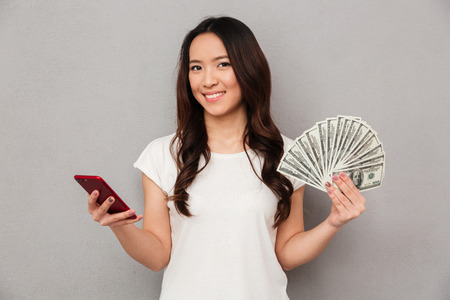 Portrait of asian brunette woman 20s holding fan of money dollar cash and cell phone in both hands isolated over gray background