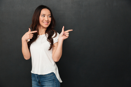 Image of joyful asian woman in casual t-shirt and jeans pointing fingers aside on copyspace text or product isolated over dark gray background Stockfoto