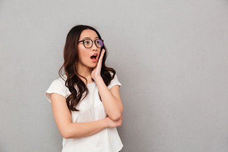Shocked asian woman in t-shirt and eyeglasses holding her cheek and looking away over black background