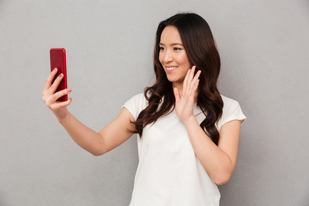 Sociable beautiful woman with asian appearance taking selfie or speaking on video call using cell phone isolated over gray background