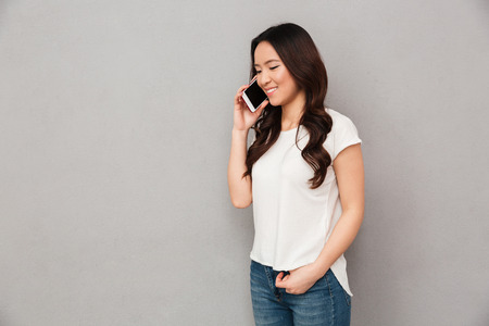Modern asian woman in casual t-shirt and jeans having mobile call using smartphone isolated over gray background Standard-Bild