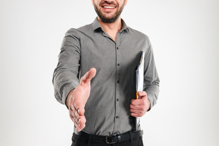 Cropped picture of cheerful businessman standing isolated over white background looking camera give you a hand for handshake.