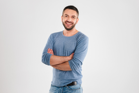 Photo of handsome happy young man standing isolated over white background wall. Looking camera. Stock Photo