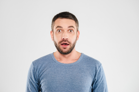 Photo of shocked young man standing isolated over white background wall. Looking camera.