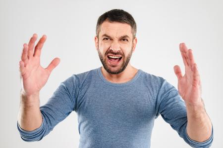 白い背景の壁の上に隔離された怒っている怒っている男の悲鳴の画像。カメラを探しています。