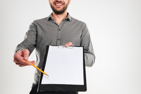 Cropped photo of businessman standing isolated over white background showing clipboard. Stock Photo