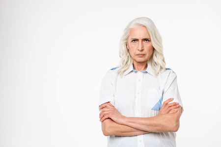 Portrait of an angry mature woman standing with arms folded isolated over white background
