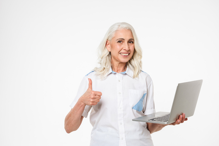 Portrait of a smiling mature woman holding laptop computer and showing thumbs up gesture isolated over white background