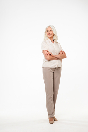 Full-lenght image of smiling mature old woman standing isolated over white background wall looking aside.