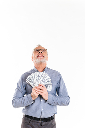 Happy mature businessman holding dollars and looking up at copy space isolated over white