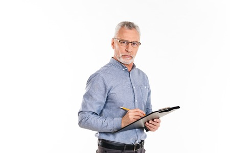 Serious confident mature man in glasses holding folder and looking camera isolated over white