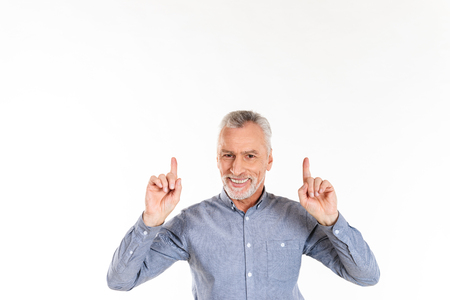 Smiling mature man in blue shirt pointing up with fingers and looking camera isolated over white