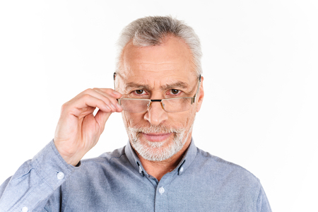 Serious mature bearded man in blue shirt holding his glasses and looking camera isolated over white Imagens