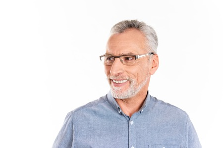 Happy mature man in glasses and blue shirt looking aside and smiling isolated over white