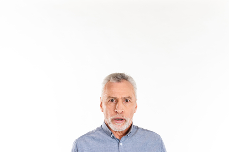 Shocked mature man looking camera with opened mouth while posing isolated over white Stock Photo