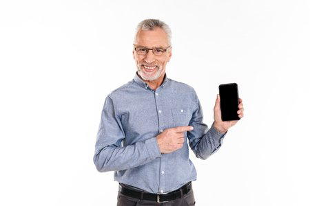 Old handsome businessman in eyeglasses pointing at blank screen of smartphone and smiling isolated Stock Photo