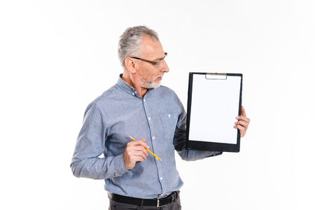 Mature concentrated man in glasses holding pencil and looking at blank folder in hands isolated over white Фото со стока