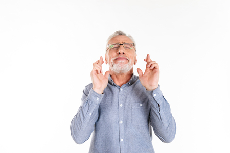 Old bearded man in glasses making pray gesture and looking up with closed eyes isolated Imagens