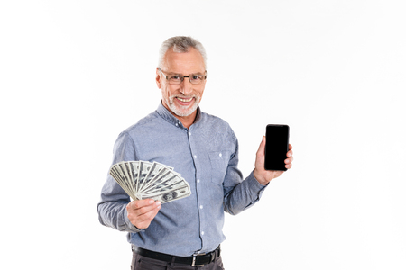 Happy old businessman showing fan of dollars and smartphone with blank screen isolated Banco de Imagens