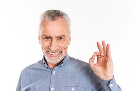 Happy mature man in blue shirt showing ok gesture and smiling to camera isolated over white
