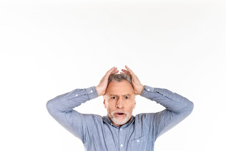Shocked mature man looking camera with opened mouth and holding his head while posing isolated over white