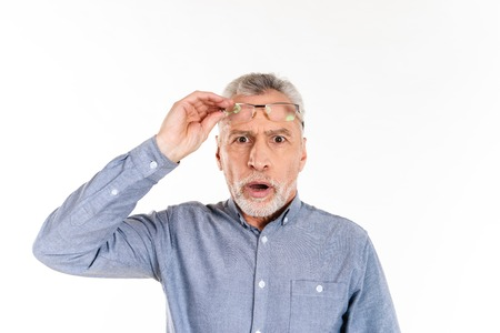 Shocked mature man in blue shirt taking off his glasses and looking camera with opened mouth isolated