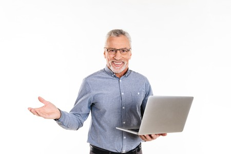 Happy old man pensioner in eyeglasses holding laptop computer and smiling to camera isolated over white