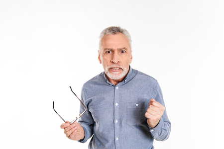 Angry displeased mature man taking off glasses and looking camera seriously isolated over white Stockfoto