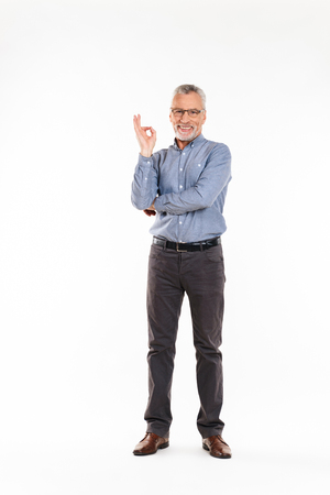 Full-length shot of old cheerful man in eyeglasses looking camera and showing ok gesture isolated over white background Stock Photo