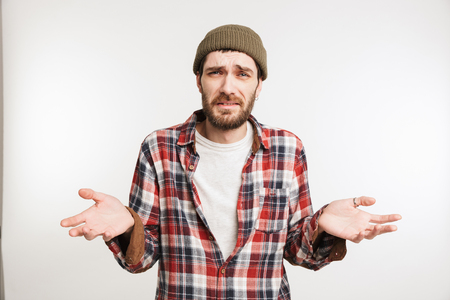 Portrait of a puzzled bearded man in plaid shirt looking at camera isolated over white background