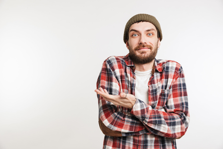 Portrait of a smiling bearded man in plaid shirt pointing away at copy space isolated over white background 스톡 콘텐츠
