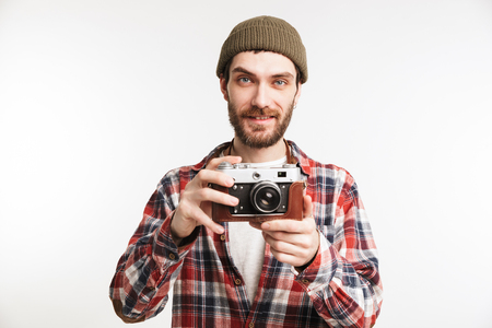 Portrait of a smiling young man tourist holding photo camera and looking at camera isolated over white background Stock Photo