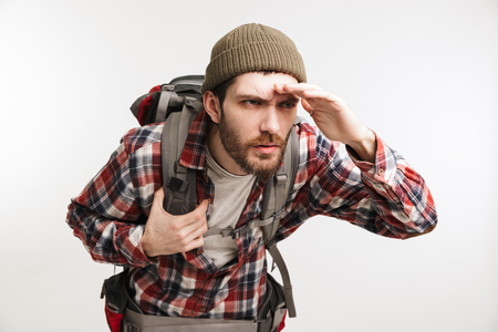 Portrait of a concentrated bearded man in plaid shirt carrying backpack and looking far away with hand on forehead isolated over white background