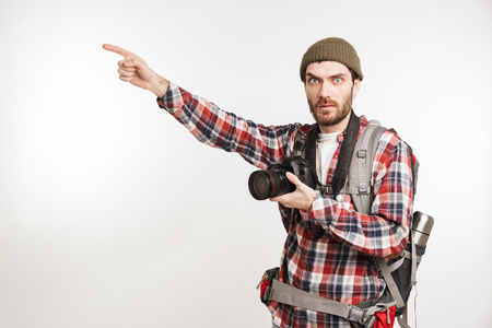 Portrait of a shocked young man tourist carrying backpack and holding photo camera pointing finger away at copy space isolated over white background