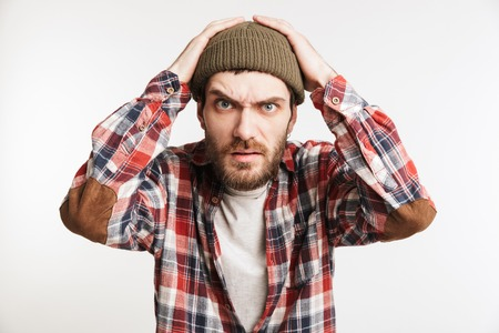Portrait of a frustrated bearded man in plaid shirt looking at camera isolated over white background