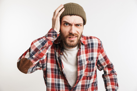 Portrait of a confused bearded man in plaid shirt looking at camera isolated over white background
