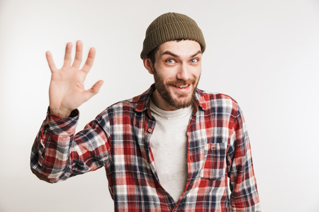 Portrait of a happy bearded man in plaid shirt waving his hand isolated over white background