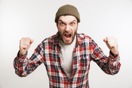Portrait of a mad bearded man in plaid shirt shouting isolated over white background
