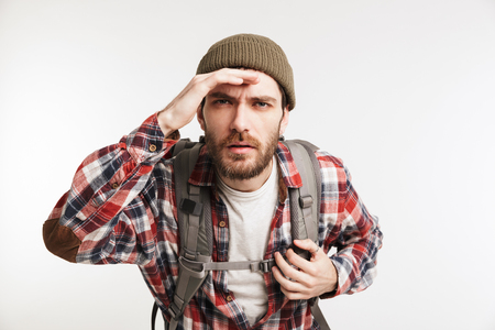 Portrait of a concentrated bearded man in plaid shirt carrying backpack and looking far away isolated over white background
