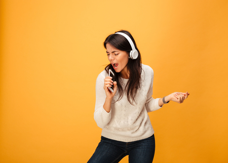 Portrait of a cheerful young woman listening to music with headphones and mobile phone isolated over yellow background