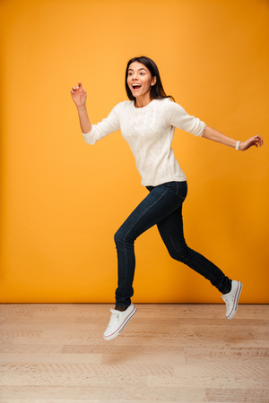 Full length portrait of a cheerful young woman jumping isolated over yellow background