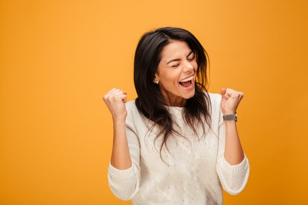 Portrait of an excited young woman celebrating success isolated over yellow background