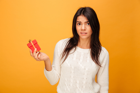 Portrait of a disappointed young woman holding small gift box isolated over yellow background