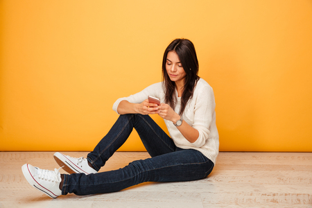Portrait of a pretty young woman sitting on a floor and using mobile phone isolated over yellow background 免版税图像