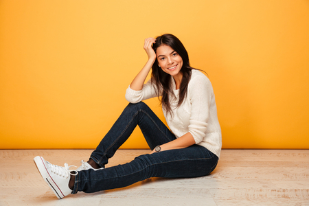Portrait of a smiling young woman sitting on a floor and looking at camera isolated over yellow background