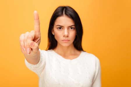 Portrait of a serious young woman showing stop gesture with a finger isolated over yellow background