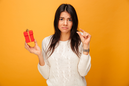 Portrait of an upset young woman holding small gift box isolated over yellow background