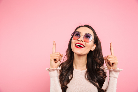 Content adult girl with red lips wearing round sunglasses looking upward and pointing fingers on copy space isolated over pink background