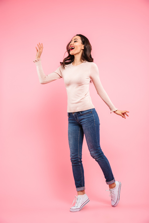 Full length photo of attractive woman 20s with long brown hair wearing jeans and sneakers rejoicing and touching copyspace isolated over pink background